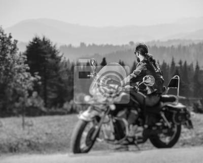 Biker de pelo largo en gafas de sol y una chaqueta de cuero sentado en una motocicleta de encargo negro y mirando a distancia. Día soleado en las montañas. Vista desde la parte posterior. Efecto de de