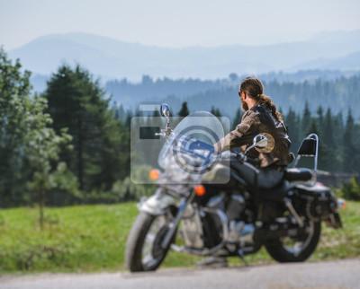 Biker de pelo largo en jeans de gafas de sol y una chaqueta de cuero sentado en una motocicleta de encargo negro y mirando a distancia. Día soleado en las montañas. Vista desde la parte posterior. Efe