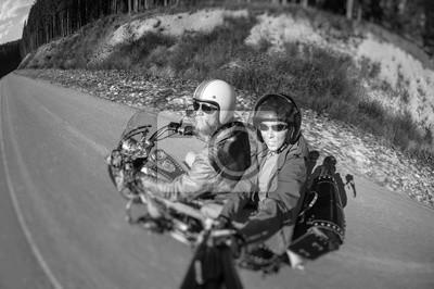 Biker montando su motocicleta en la carretera con el pasajero mirando a la cámara. El hombre está usando chaqueta, casco y gafas de sol. Estilo de Selfie. Imagen en movimiento. Efecto de desenfoque de