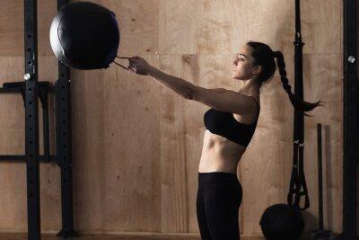 Póster Bola del peso de la elevación de la mujer en el gym