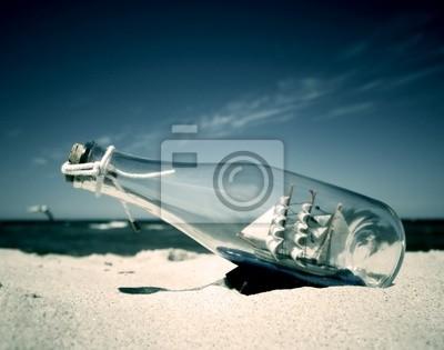 Botella con la nave en el interior tumbado en la playa. Imagen conceptual