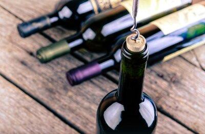 Póster Botella de vino en una mesa de madera