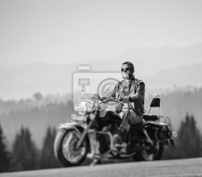 Brutal biker con barba en gafas de sol, jeans y una chaqueta de cuero sentado en la moto de viaje. Día soleado en las montañas. Efecto suave de cambio de inclinación. en blanco y negro
