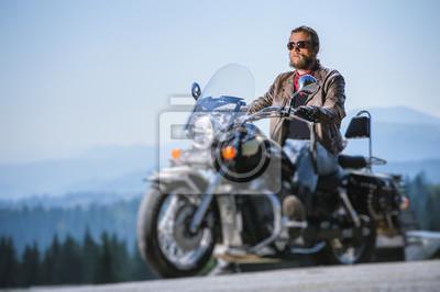 Brutal hombre con barba en gafas de sol, blue jeans y una chaqueta de cuero sentado en la moto de viaje. Día soleado en las montañas. Efecto suave de cambio de inclinación