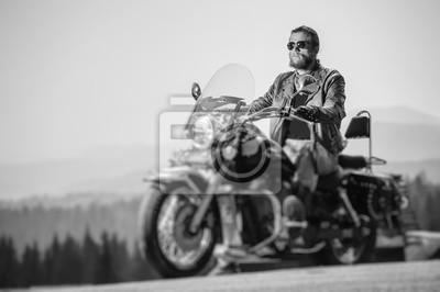 Brutal hombre con barba en gafas de sol, jeans y una chaqueta de cuero sentado en la moto de viaje. Día soleado en las montañas. Efecto suave de cambio de inclinación. En blanco y negro