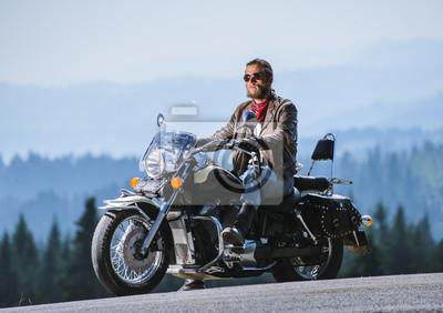 Brutal joven con barba en gafas de sol, blue jeans y una chaqueta de cuero sentado en la moto de viaje. Día soleado en las montañas