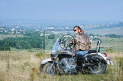 Brutal motociclista con barba vistiendo chaqueta de cuero y gafas de sol sentado en su motocicleta en un día soleado. Imagen horizontal. Vista desde la parte posterior. Mirando a la cámara. Efecto de