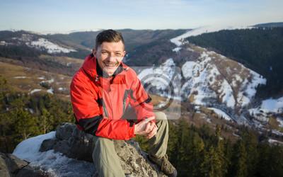 Caminante sentado en la roca grande en la cima de la montaña