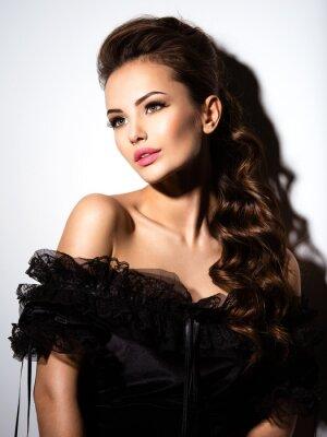 Póster Cara hermosa de una muchacha atractiva joven en alineada negra