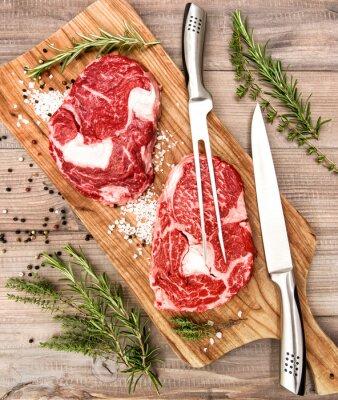 Póster Carne fresca cruda Steak Ribeye con hierbas y especias en el escritorio de madera