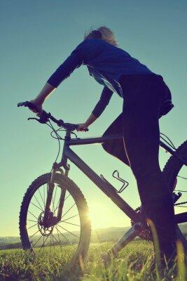 Póster Chica en una bicicleta en la puesta de sol