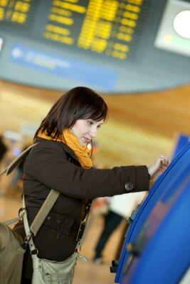 Chica haciendo auto-checkin en el aeropuerto