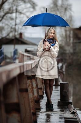 Chica joven en un puente en un día de lluvia y nubes