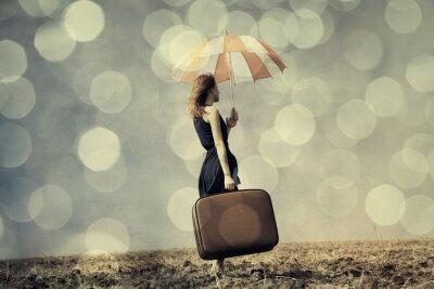 Póster Chica pelirroja con paraguas y maleta en el campo ventoso