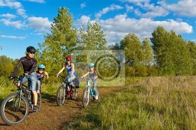 Ciclismo Familia al aire libre. Padres felices con dos niños en bicicleta