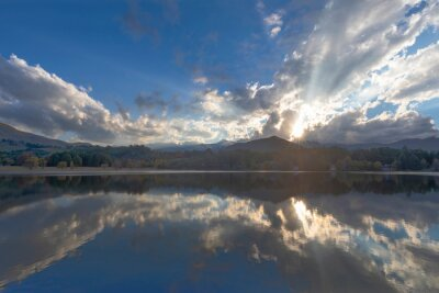 Clouds and rays of the sun reflect on the pond