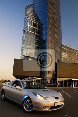 Coche deportivo con edificio de oficinas y el cielo azul claro detrás de él