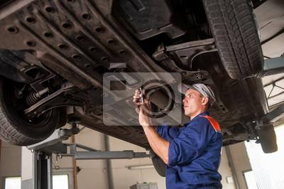 Coche mecánico examinando levantó el coche en la estación de servicio de reparación. Usi