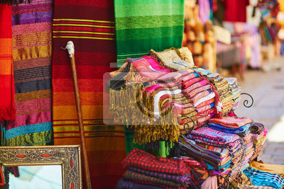 Colorful fabrics and carpets for sale on a street in Medina