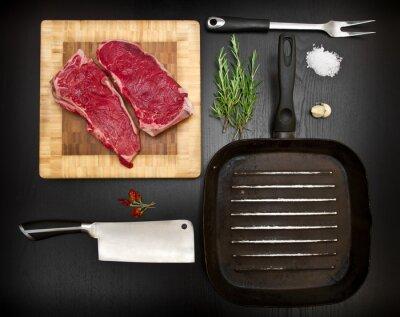 Póster Composición con costillas en bruto y herramientas de cocina en madera negra