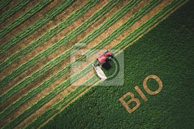 Concepto bio y tactor cortando campo verde