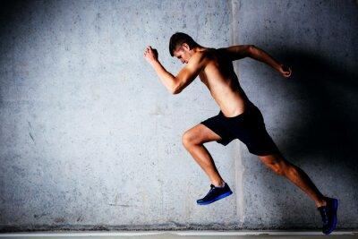Póster Corredor de sprinting contra la pared de hormigón en el garaje