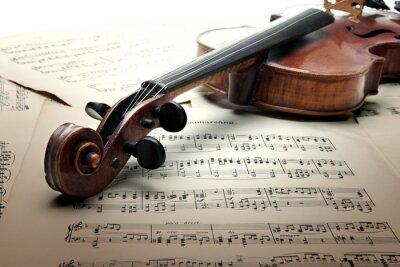 Cuello del violín con clavijero y scrool, en la hoja de música.