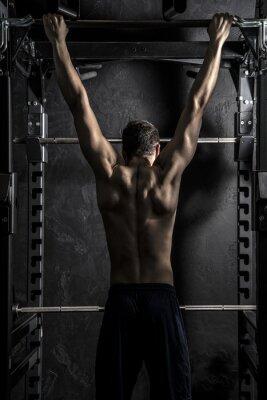 Póster Culturismo, joven atlético Hombre fuerte que muestra los músculos posteriores de trabajo en Fitness Bar, Contraste fuerte con filtro Desaturated Grunge