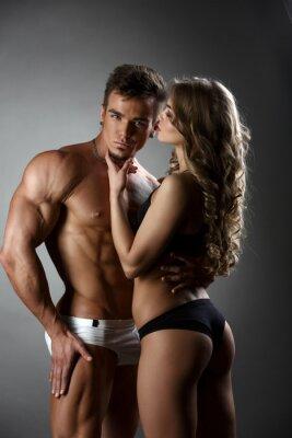 Póster Culturista sexual abraza chica posesivamente
