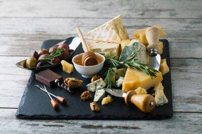 Póster Deliciosos quesos en un tablero con miel, nueces en un backgro blanco