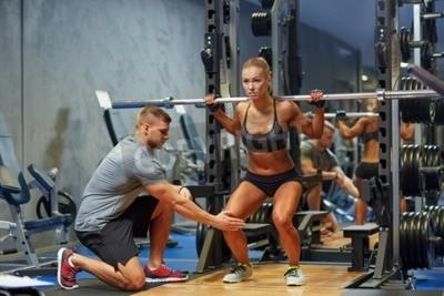Póster Deporte, aptitud, trabajo en equipo, culturismo y concepto de la gente - mujer joven y entrenador personal con la barra flexionando los músculos en el gimnasio