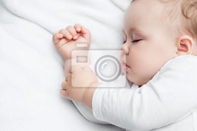 Despreocupado dormir pequeño bebé en una cama