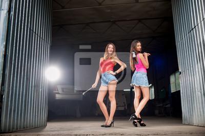 Dos hermosas chicas sexy de pie en la entrada a la reparación de coches