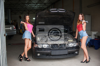 Dos hermosas chicas sexy de pie por el coche con la tapa abierta sostener