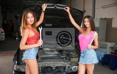 Dos hermosas mujeres jóvenes de pie cerca de coche con la tapa abierta sostener