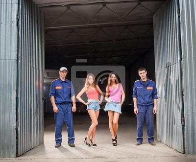 Dos hombre mecánico de automóviles y dos hermosas chicas sexy de pie en t