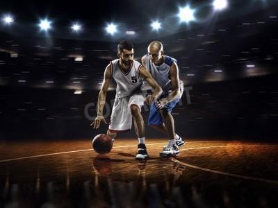 Póster Dos jugadores de baloncesto en la acción en el gimnasio en las luces