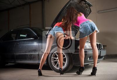 Dos muchachas atractivas que examinan el motor de coche en la tienda de reparación auto