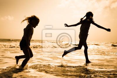 dos siluetas de niños corriendo en la playa al atardecer