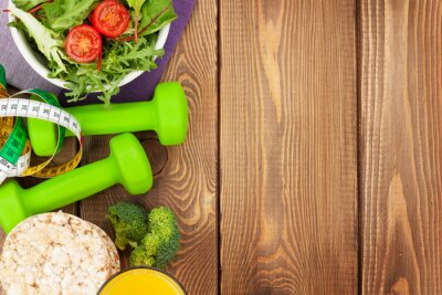 Póster Dumbells, tape measure and healthy food over wooden table