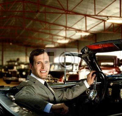 El hombre detrás de la rueda de un coche retro