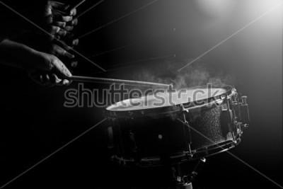 Póster El hombre está tocando el tambor en el fondo de poca luz.