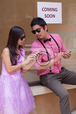 el hombre y la mujer con el teléfono móvil en la mano para el acto de la comedia