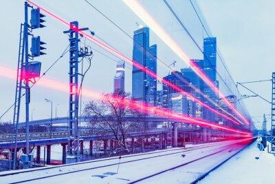 El moderno tren de alta velocidad se mueve rápido en el fondo del centro de negocios en la noche de invierno.