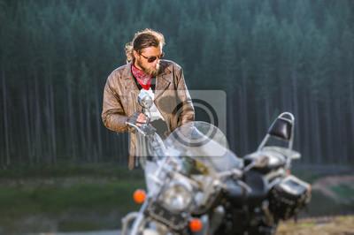 El motorista joven hermoso se está sentando abajo en su moto larga del recorrido de la distancia con el bosque en el fondo. El hombre lleva chaqueta de cuero y gafas de sol. Efecto de desenfoque de la