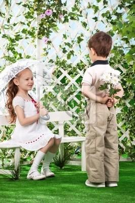 El muchacho da a muchacha las flores, sentado en un banco en el jardín