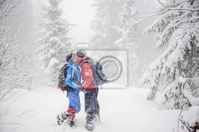 El muchacho y la muchacha que se coloca en maderas nevadas y besos