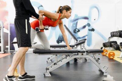 Póster Entrenador masculino joven dando instrucciones a una mujer en un gimnasio