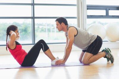 Póster Entrenador mujer de ayuda abdominales en el gimnasio