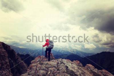 Póster exitosa mujer mochilero disfrutar de la vista y la cima de la montaña